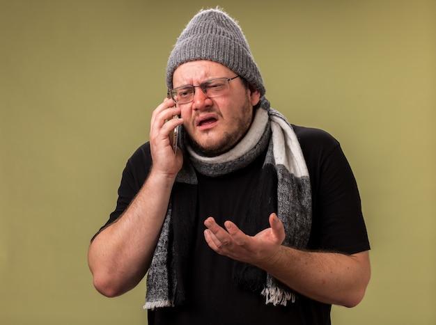 Verward kijkende zieke man van middelbare leeftijd met wintermuts en sjaal spreekt aan de telefoon