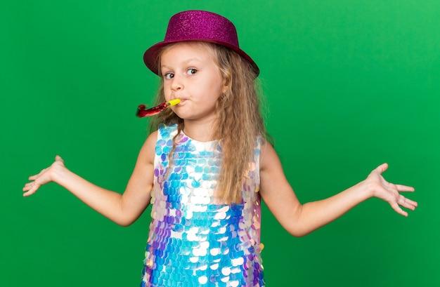 Verward klein blond meisje met paarse feestmuts die feestfluit blaast en handen open houdt geïsoleerd op groene muur met kopieerruimte