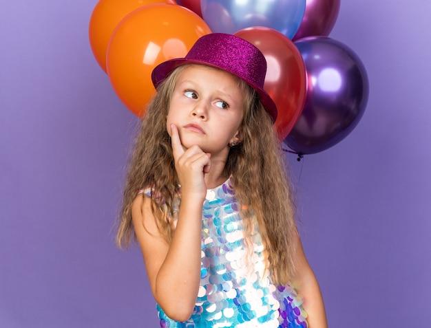 Verward klein blond meisje met violette feestmuts vinger op kin zetten en kijken naar kant staande voor helium ballonnen geïsoleerd op paarse muur met kopie ruimte