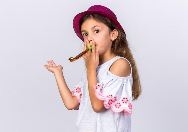 Verward klein kaukasisch meisje met paarse feestmuts die feestfluit blaast en hand open houdt geïsoleerd op een witte muur met kopieerruimte