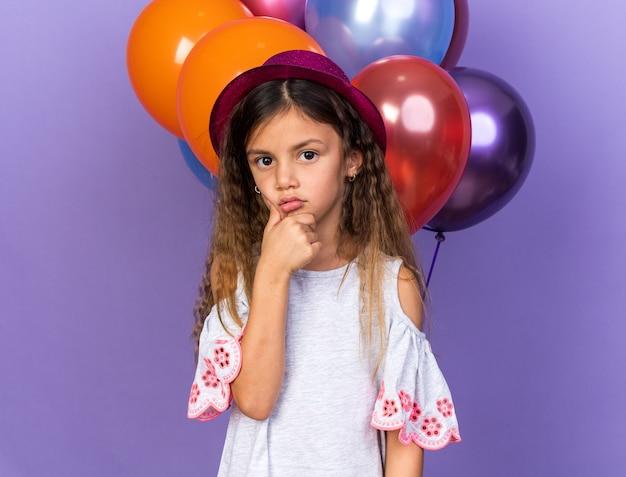 Verward klein kaukasisch meisje met violet feestmuts met kin staande voor heliumballonnen geïsoleerd op paarse muur met kopieerruimte
