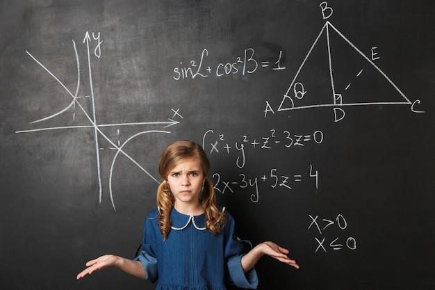 Verward klein schoolmeisje dat bij het bord staat met wiskundige afbeeldingen erop geschreven