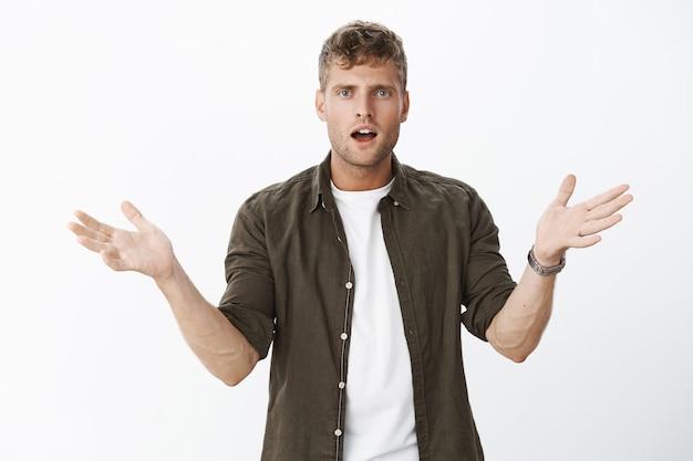 Verward knappe blonde man met blauwe ogen die handen zijwaarts opheffen in ontzetting en geen idee gebaar onverwacht gedumpt staande ondervraagd en teleurgesteld over grijze muur