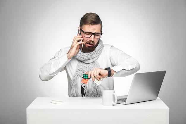 Verward koude zieke jonge msn in wit overhemd en sjaal zitten op kantoor op het bureau en praten met partner aan de telefoon, ook de tijd controlerend op zijn eigen handhorloge, het plannen van een vergadering. binnen grijze achtergrond