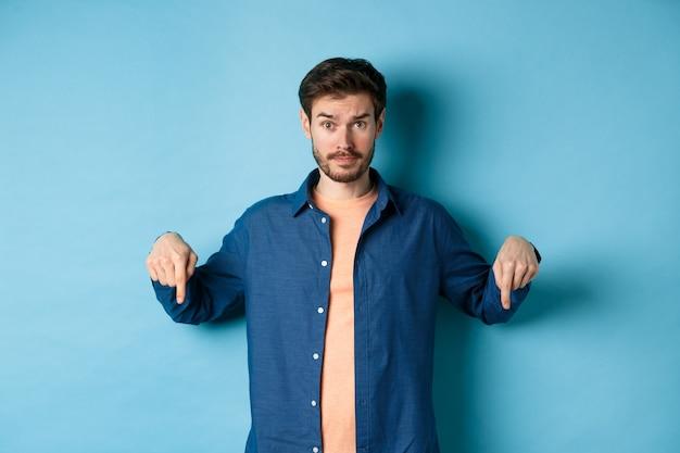 Verward mannelijk model in vrijetijdskleding, verbaasd kijkend en wijzende vingers naar beneden, banner tonen, staande op blauwe achtergrond.