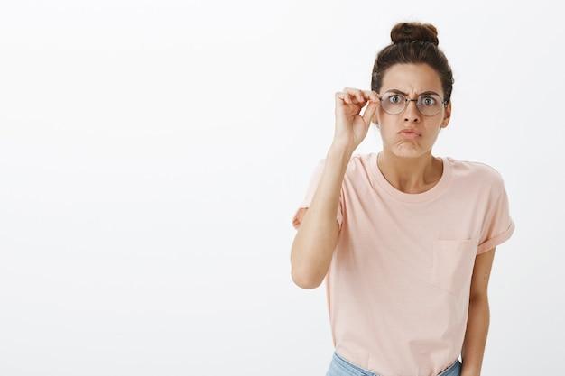 Verward meisje met bril poseren tegen de witte muur