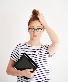 Verward meisje met tablet die op haar hoofd krabt