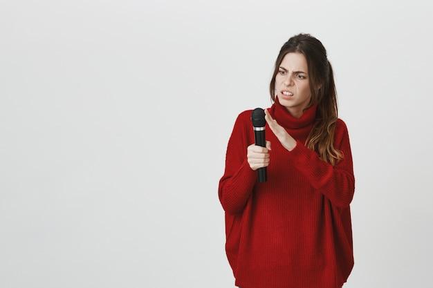 Verward meisje touch microfoon, controleer of het werkt