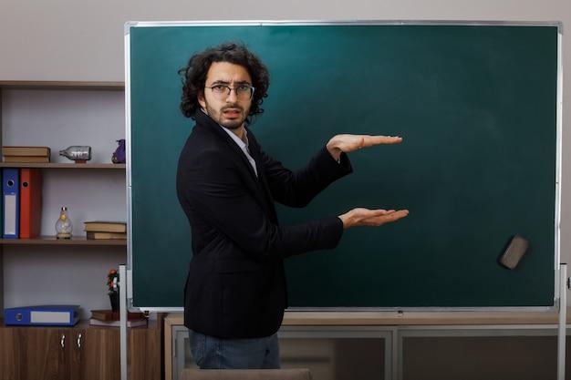 Verward met het tonen van de grootte van een jonge mannelijke leraar die vooraan op het schoolbord staat in de klas