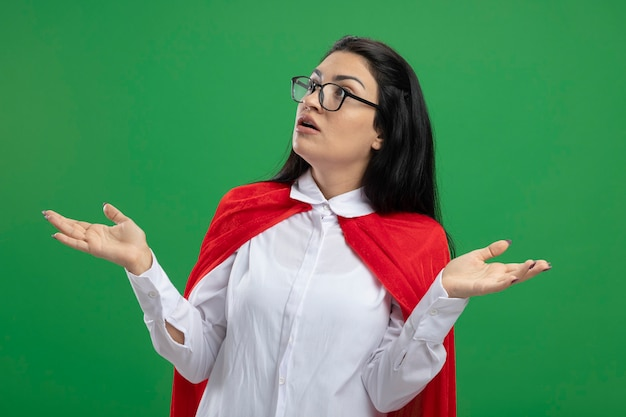 Verward misverstand jonge supervrouw die een bril draagt die lege handen omhoog houdt en niet begrijpt wat er aan de hand is er recht uit te zien geïsoleerd op groene muur