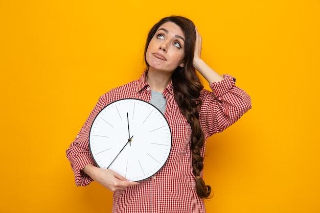 Verward mooie blanke schonere vrouw die klok vasthoudt en hand op haar hoofd legt terwijl ze omhoog kijkt
