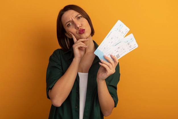 Verward mooie blanke vrouw legt vinger op gezicht en houdt vliegtickets op oranje