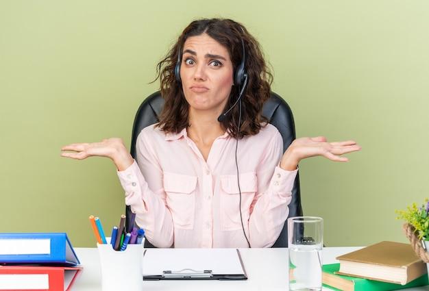 Verward mooie blanke vrouwelijke callcenter-operator op koptelefoon zittend aan bureau met kantoorhulpmiddelen die handen open houden geïsoleerd op groene muur