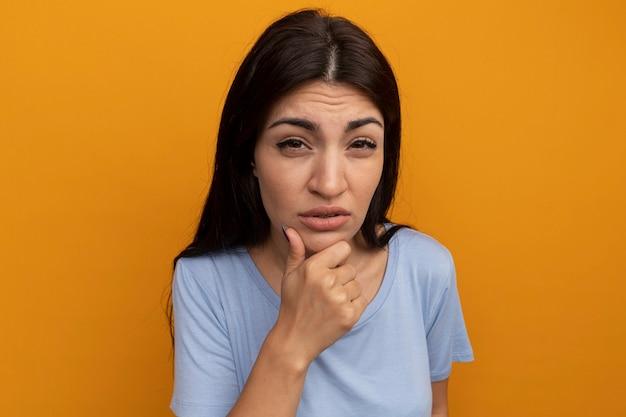Verward mooie brunette vrouw houdt kin en kijkt naar voorzijde geïsoleerd op oranje muur