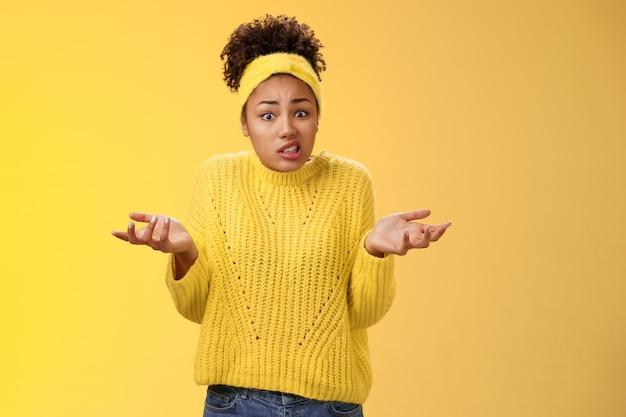 Verward onhandige schattige vrouwelijke werknemer verknalde papieren verloren papierwerk schouderophalend handen opsteken onzeker zeg oeps ineenkrimpen ongemakkelijk staan geen idee wat er gebeurt, gele achtergrond.