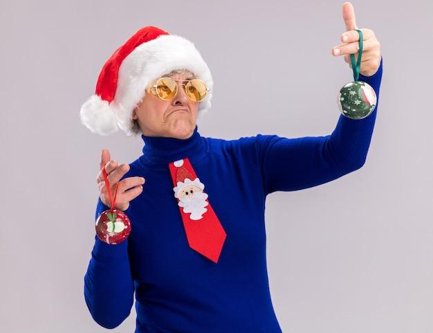 Verward oudere vrouw in zonnebril met kerstmuts en santa stropdas houden en kijken naar glazen bol ornamenten geïsoleerd op een witte muur met kopie ruimte