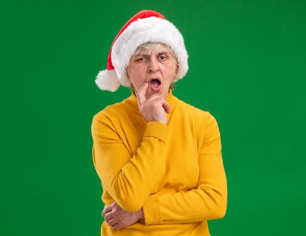 Verward oudere vrouw met kerstmuts legt vinger op kin geïsoleerd op paarse achtergrond met kopie ruimte