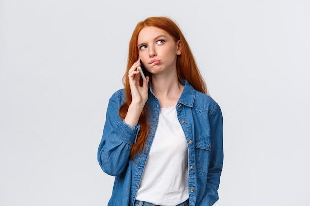 Verward over beslissingen. weet niet zeker schattige roodharige vrouw om af te halen in favoriete restaurant, iemand aan de telefoon te bellen, er attent uit te zien, te denken, nadenkend antwoord te geven tijdens het praten, smartphone vasthouden