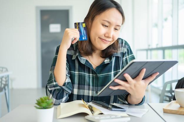 Verward portret van jonge vrouwenholding creditcards die probleem online betaling hebben