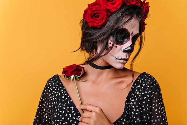 Verward romantisch meisje met gezichtskunst in de vorm van een schedel houdt roos op sleutelbeen vast. brunette poseren in zwarte top op oranje muur.
