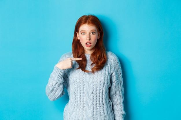 Verward roodharig meisje wijzend op zichzelf, wordt gekozen, staande in trui tegen blauwe achtergrond
