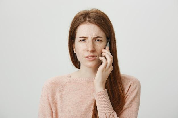 Verward roodharige vrouw fronsend perplex als praten over de mobiele telefoon