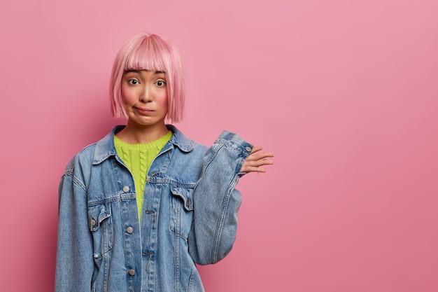 Verward roze harige vrouw steekt hand op en staat niet op de hoogte, heeft een stijlvol kapsel, gekleed in spijkerkleding, heeft geen idee, staat voor dilemma, poseert