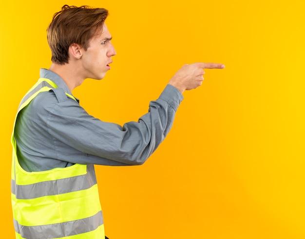 Verward staande in profiel weergave jonge bouwer man in uniforme punten aan de zijkant geïsoleerd op gele muur met kopieerruimte