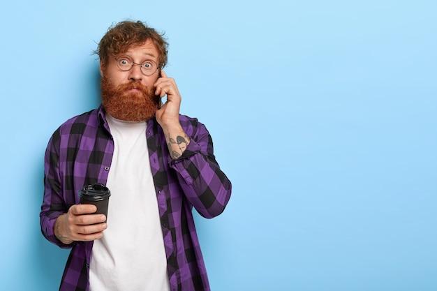 Verward stijlvolle gember man poseren tegen de blauwe muur