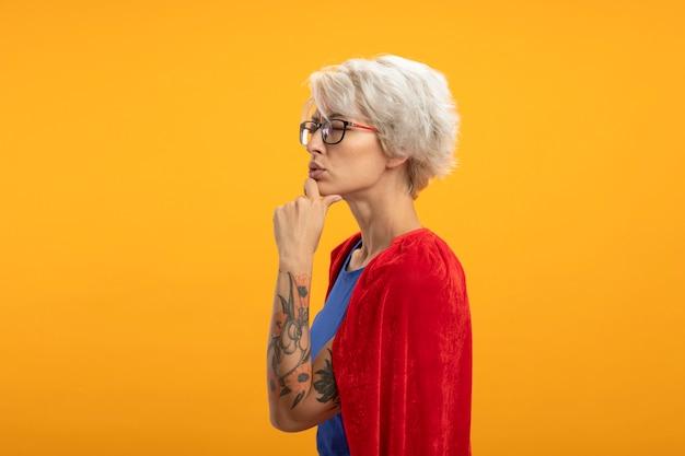 Verward supervrouw met rode cape in optische glazen staat zijwaarts hand op kin geïsoleerd op oranje muur te zetten