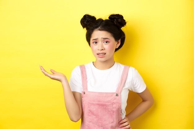 Verward tiener aziatisch meisje met lichte make-up en zomerkleding, hand opsteken en verbaasd fronsen, kan het niet begrijpen, geel.