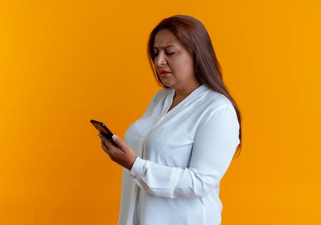 Verward toevallige kaukasische vrouw die op middelbare leeftijd en telefoon houdt bekijkt