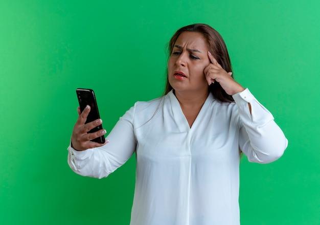 Verward toevallige kaukasische vrouw van middelbare leeftijd die en telefoon bekijkt die vinger op voorhoofd zetten