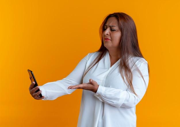 Verward toevallige kaukasische vrouwenholding op middelbare leeftijd en punten met hand aan telefoon