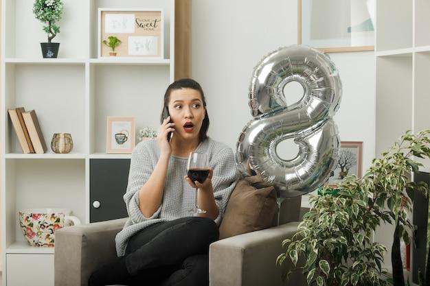 Verward uitziende kant mooie vrouw op gelukkige vrouwendag met glas wijn spreekt over wijn zittend op een fauteuil in de woonkamer