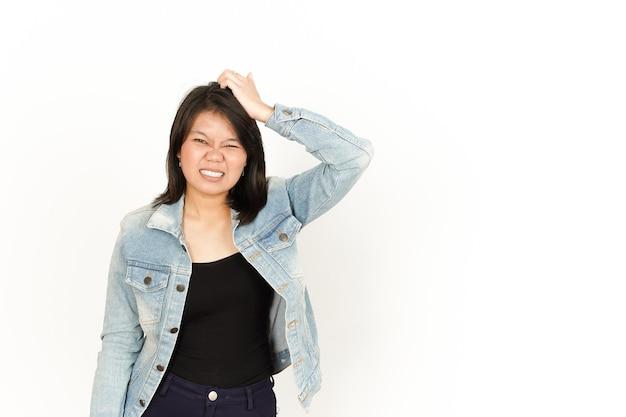 Verward van mooie aziatische vrouw die jeansjasje en zwart overhemd draagt dat op witte achtergrond wordt geïsoleerd