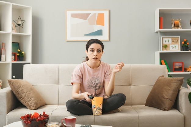 Verward verspreidende hand jong meisje met tv-afstandsbediening, zittend op de bank achter de salontafel in de woonkamer