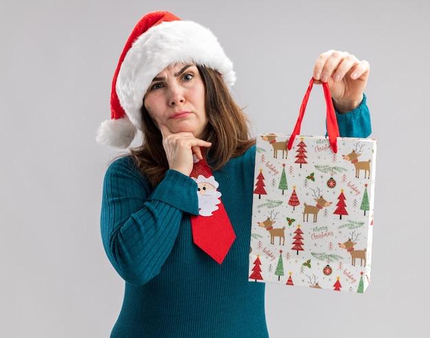 Verward volwassen blanke vrouw met kerstmuts en santa stropdas zet vinger op kin en houdt papieren geschenkdoos geïsoleerd op een witte muur met kopie ruimte