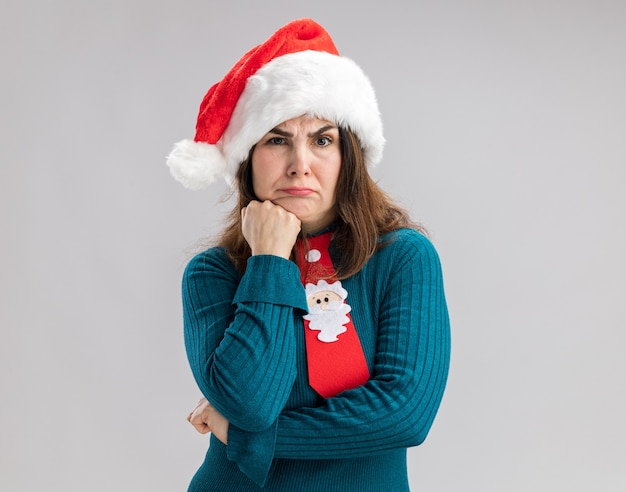 Verward volwassen blanke vrouw met kerstmuts en santa stropdas zet vuist op kin geïsoleerd op een witte muur met kopie ruimte