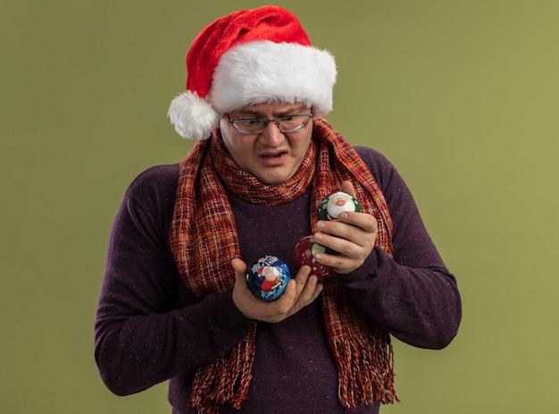 Verward volwassen man met bril en kerstmuts met sjaal om nek houden en kijken naar kerstballen geïsoleerd op olijf groene muur