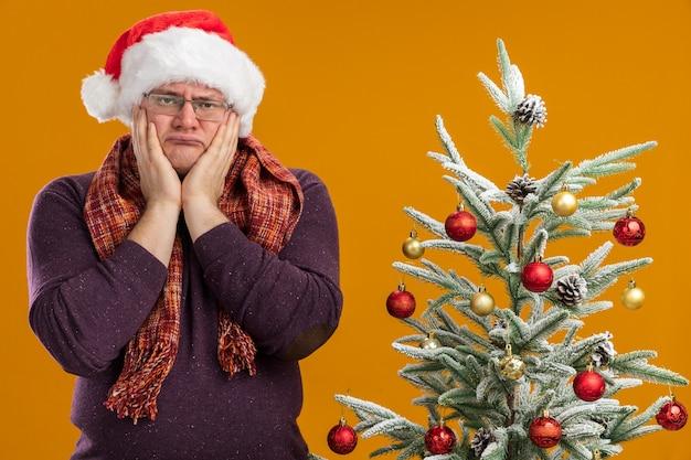 Verward volwassen man met bril en kerstmuts met sjaal om nek staande in de buurt van versierde kerstboom houden handen op gezicht geïsoleerd op oranje muur