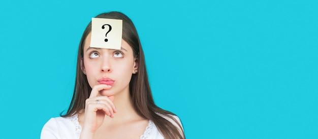 Verward vrouwelijk denken met vraagteken op kleverige nota op voorhoofd. denkende vrouw die met vraagteken omhoog kijkt. twijfelachtig meisje dat vragen aan zichzelf stelt. papieren notities met vraagtekens.