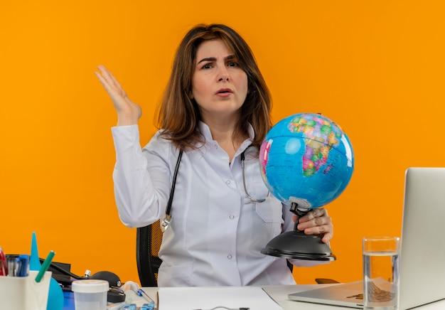 Verward vrouwelijke arts van middelbare leeftijd die medische mantel draagt met een stethoscoop zittend aan een bureau werkt op laptop met medische hulpmiddelen die bol houdt en hand verspreidt op geïsoleerde oranje muur met kopie ruimte
