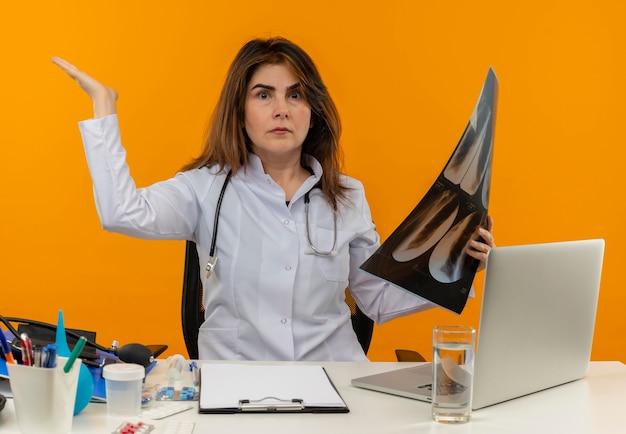 Verward vrouwelijke arts van middelbare leeftijd die medische mantel met stethoscoop draagt die aan bureau zit werkt op laptop met medische hulpmiddelen die röntgenfoto houdt en hand op geïsoleerde oranje muur opheft