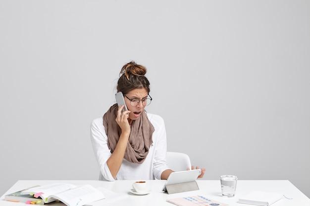 Verward vrouwelijke kantoormedewerker heeft wat problemen met werken op tablet, monteur belt, probeert probleem op te lossen
