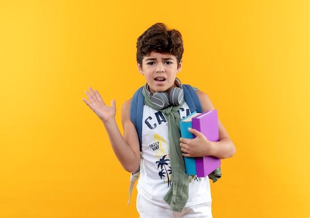Verward weinig schooljongen die rugtas en koptelefoon draagt die boeken en punten met hand aan kant houdt die op gele achtergrond met exemplaarruimte wordt geïsoleerd