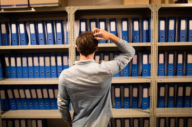 Verward zakenman op zoek naar bestanden op de kast in de opslagruimte