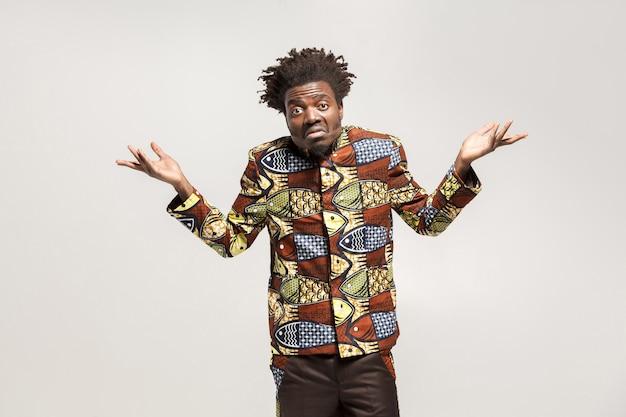 Verwarde afro man verbaasd en zeggen weet het niet, misschien. binnen, geïsoleerd op grijze achtergrond
