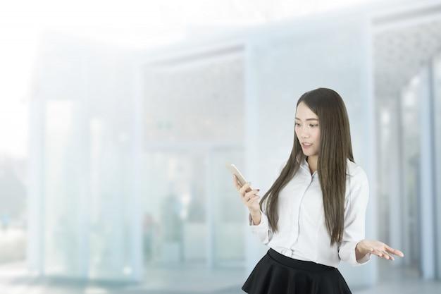 Verwarde aziatische onderneemster die smartphone gebruikt.