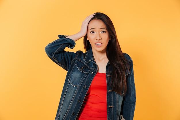 Verwarde aziatische vrouw die in denimjasje haar hoofd houdt